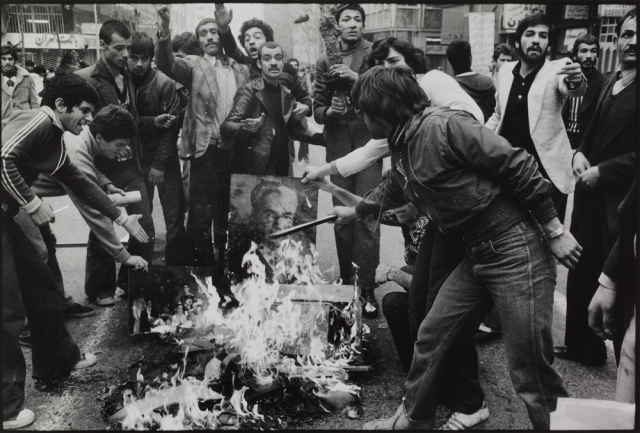 Abbas, 'Rioters burn a portrait of the Shah as a sign of protest against his regime. Tehran,December 1978', from the series Iran Diary, 1978-9, courtesy V&A